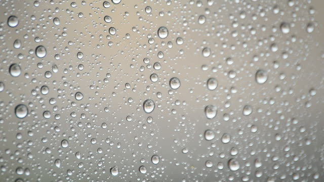 Raindrops sliding down the glass window of a room video