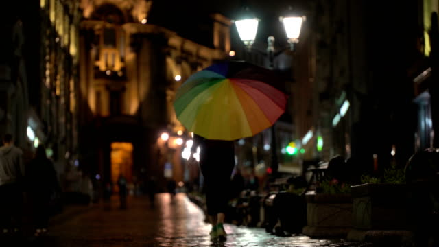 Rainy evening in the city, street with street lights, shiny asphalt from the rain. Unrecognizable pedestrians, young people, among whom is pretty girl with colorful umbrella. Concept of leisure, seasons, weather, lifestyle of modern city video