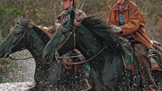 SLO MO TD Ranchers on galloping horses crossing river video