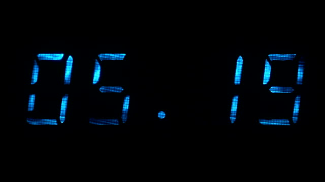 Rapid adjustment of time on the digital clock display, blue digits on a black video