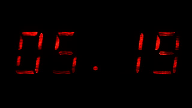 Rapid adjustment of time on the digital clock display, red digits on a black video