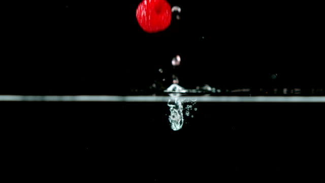 Raspberries falling in water on black background video