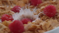 Raspberries splashing into bowl of cereal in slow motion video