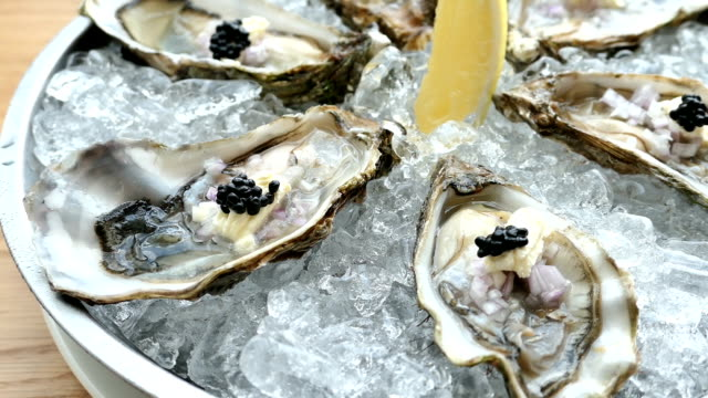 Raw and fresh Oyster with caviar on top and lemon video