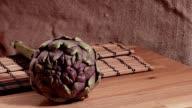 Raw artichoke on wooden cutting board video