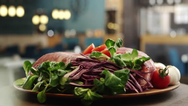 Raw beef steak with ingredients beside video