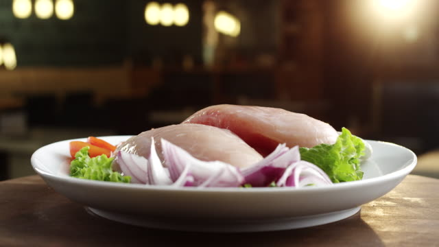 Raw chicken breast on plate with lettuce, onion and tomato video