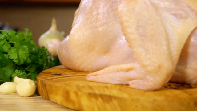 Raw chicken on a wooden cutting board sprinkled with spices video