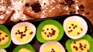 Raw dough for muffins in special paper baking dish sprinkled with chocolate pieces video