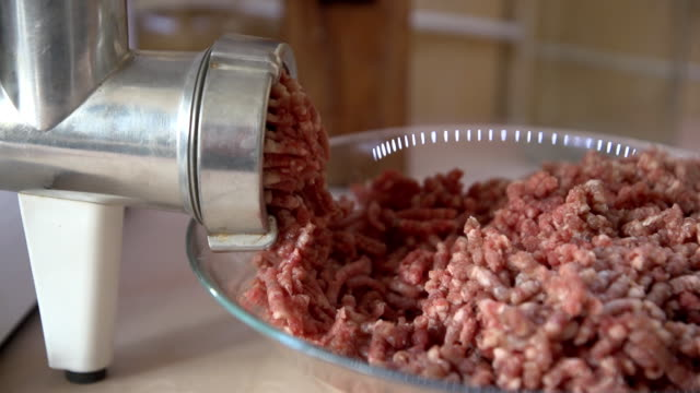 Raw meat minced meat falls from a metal grinder into a glass cup. video