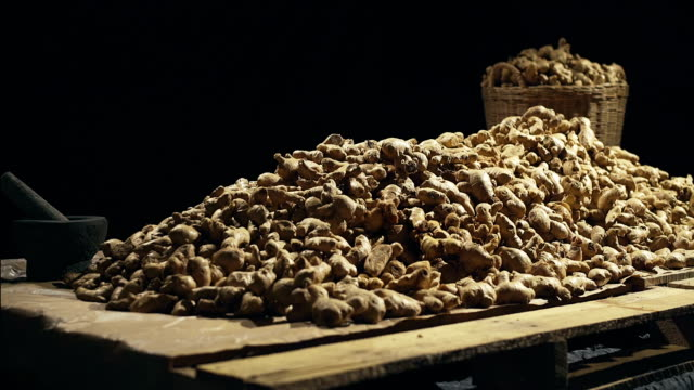 Raw Organic Ginger root with Stone mortar and pestle over black background video