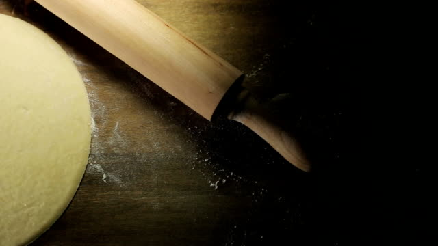 Raw pizza dough, a rolling pin on a wooden surface video