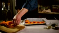 Raw pumpkin pieces ready for baking. Chef put pumpkin slices on baking tray video