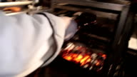 Raw steak being placed on flaming charcoal grill by cook video