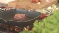 Raw steak grilling on frying pan video