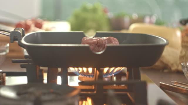 Raw steak grilling on frying pan video