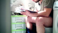 Reading a magazine in bathroom. video