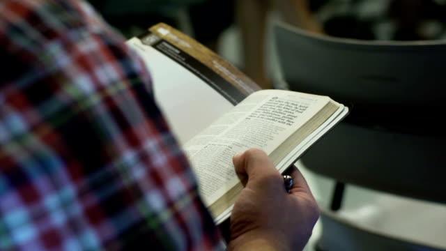 Reading an open Bible during church video