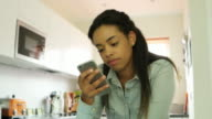 Reading phone message. Young woman, kitchen. video