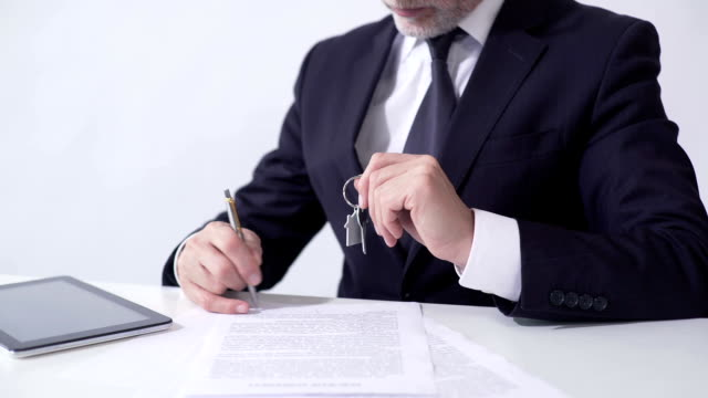 Real estate agent holding out house keys to client and signing mortgage papers video