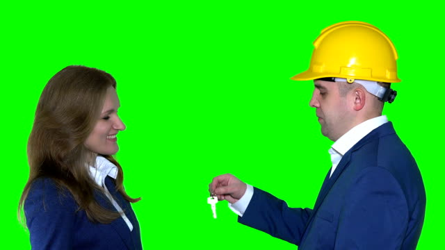 real estate agent man with helmet give new flat house keys to happy client woman video