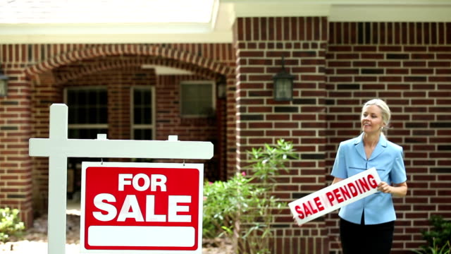 Real estate agent places 'sale pending' sign. Home for sale. video