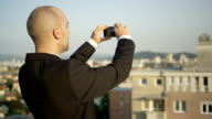 CLOSE UP: Real estate agent taking pictures of building on market from outside video