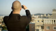 CLOSE UP: Real estate businessman taking pictures of houses standing on rooftop video