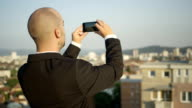 CLOSE UP: Real estate manager taking pictures of houses standing on the rooftop video