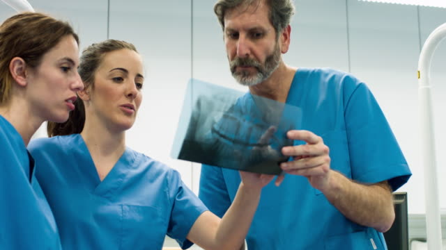 Real time video of group of dentist looking to x-ray image at dental clinic video