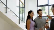 Real-estate agent giving keys to couple video