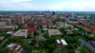 Really Far Wide Angle Campus UT Tower Aerial Fly by Austin Texas Over University of Texas at Austin Capital Cities with Downtown Cityscape Skyline in the background at Center moving forwards close with Pool and Amazing Architecture and Church in View video