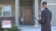 Realtor in front of home with notebook video