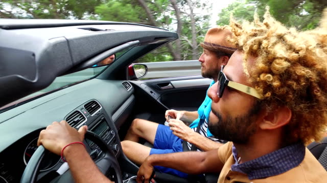 Rear mirror view of handsome black men driving his friends in convertible video