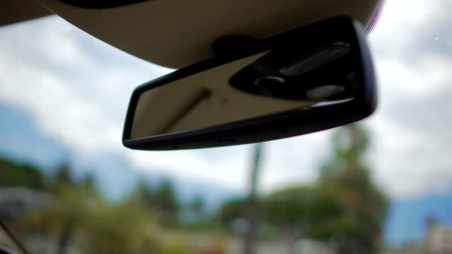 Rear view mirror close-up, person travelling by car, driving in the city video