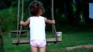Rear view of a child playing with a rope swing video