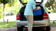 Rear view of a man placing his cooler in his car video