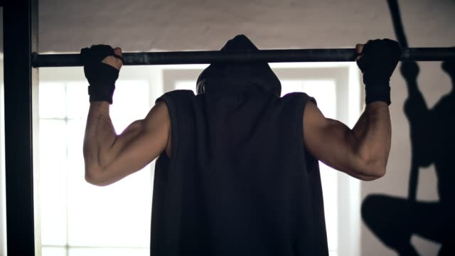 Rear view of a man training on chin-up bar video