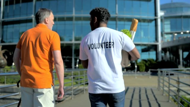 Rear view of an active volunteer helping a senior man video
