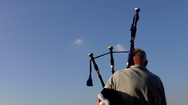 Rear view of an old man playing bagpipes isolated video