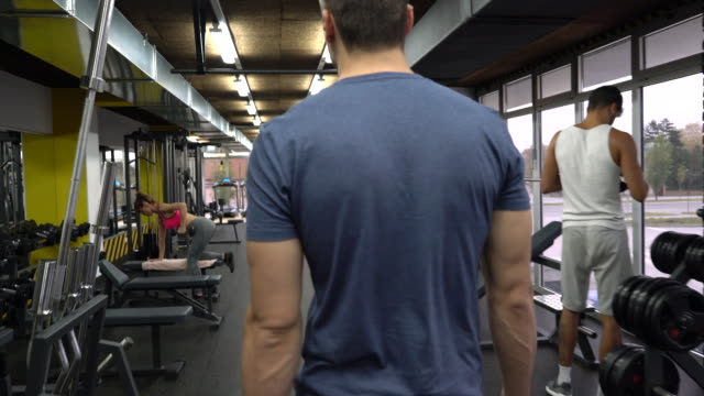 Rear view of athletic man walking through the gym. video