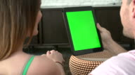 Rear View Of Couple Sitting On Sofa Using Digital Tablet video
