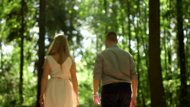 MEDIUM SHOT TRACKING SHOT Rear view of couple walking in forest on sunny day video