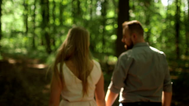 MEDIUM SHOT TRACKING SHOT TILT DOWN Rear view of couple walking in forest on sunny day video