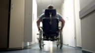 Rear view of disabled man pushes himself in wheelchair down hospital corridor video