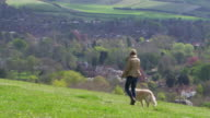 Rear View Of Woman Taking Dog For Walk Shot On R3D video