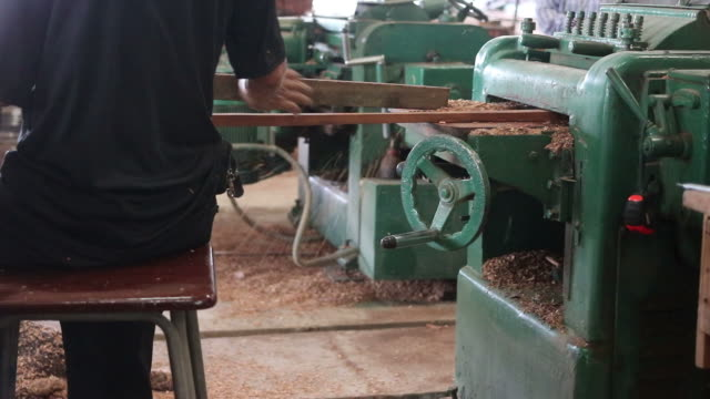Rear view of worker is working with electric planer of wood machine. video