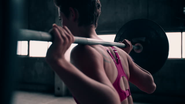 Rearview of a girl lifting a barbell with heavy weights video