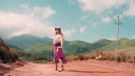 Rearview of boho girl walking down a country dirt road video