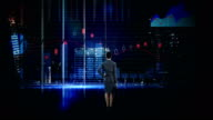 Rearview of businesswoman looking at digital animation of glowing graph interface video